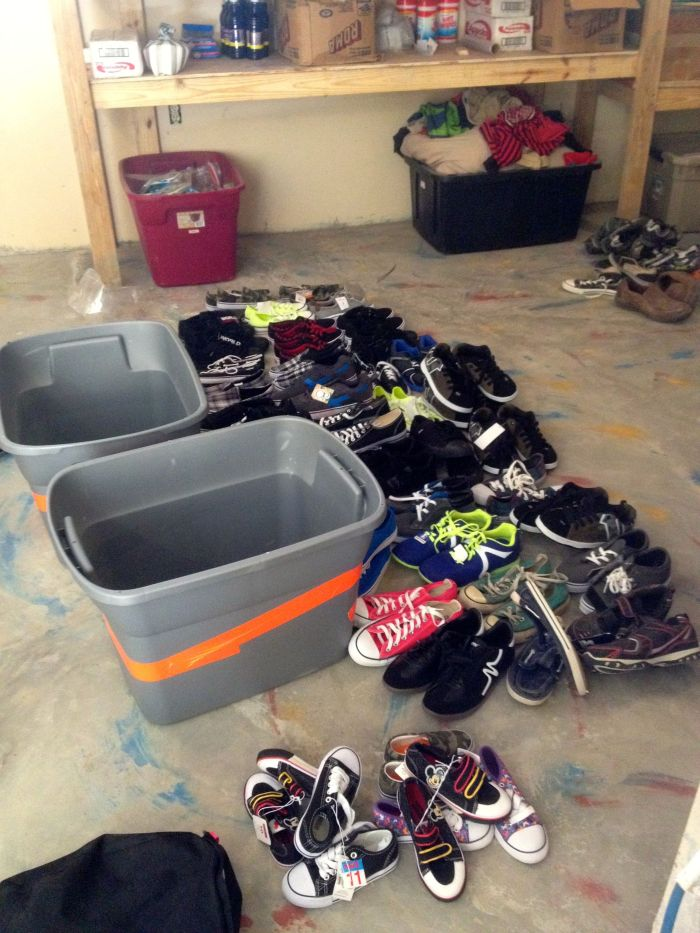 Sorting shoes by size for the younger kids at the Thozin site in the storage depot